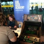 KTS's Quarries of Scred arcade machine right next to Emily from Geek Girl Academy